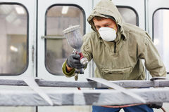 Man in protective clothes works in paint-spraying booth. Man in protective clothes and respirator works in paint-spraying booth, painting car details Royalty Free Stock Photography