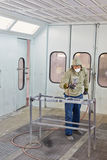 Man in protective clothes works in paint-spraying booth. Man in protective clothes and respirator works in paint-spraying booth, painting car details with royalty free stock photos