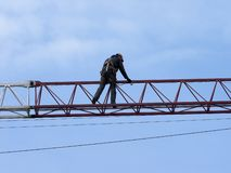 Man in protective clothing on the arm of the crane against the b stock photo