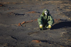 Man in protective clothing sitting in desert Stock Image