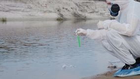 Man in a protective costume and gas mask of respirator observes a chemical reaction of water in test tube. Which he took for analysis from a polluted river stock video