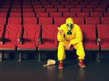 The  man in a protective coverall. The man in a protective coverall  sitting in an empty theater. Creative concept Stock Photography