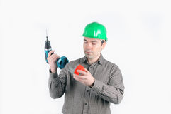 Man in protective helmet connects the battery to d Royalty Free Stock Photos