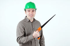 Man in protective helmet with a handsaw Stock Photography