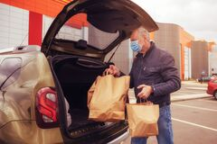A man with a protective mask on his face loads food packages into the car. Food delivery