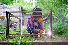 Man in a protective mask welding metal construction outside on a summer day Royalty Free Stock Photos
