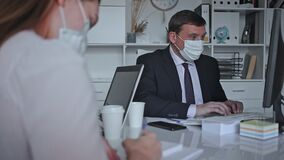Man in protective medical mask helping his colleague to prepare document