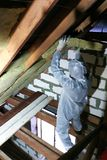 A man in a protective overalls puts mineral wool between the beam of the roof of the house for his warming from the cold stock photos