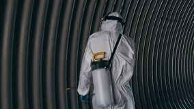 Man in protective suit disinfects subway tunnel with an antiseptic sprayer. Surface treatment due to coronavirus covid