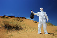Man in a protective suit holding a waste bag Stock Photos