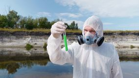 Man in a protective suit and respirator observes a chemical reaction of water in test tube. Which he took for analysis from polluted river, then rises and stock video
