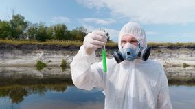 Man in a protective suit and respirator observes a chemical reaction of water in test tube. Which he took for analysis from polluted river, then leaves stock video