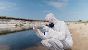 Man in a protective suit and respirator observes a chemical reaction of water in test tube. Which he took for analysis from polluted river. Scientist takes stock video footage