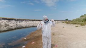 Man in a protective suit and respirator observes a chemical reaction of water in test tube. Which he took for analysis from polluted river, then looks to stock footage
