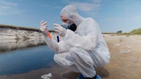Man in a protective suit and respirator observes a chemical reaction of water in test tube. Which he took for analysis from polluted river. Scientist takes stock video