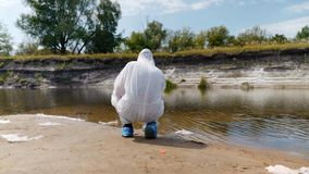 Man in a protective suit and respirator observes a chemical reaction of water in test tube. Which he took for analysis from polluted river. Scientist takes stock footage
