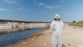 Man in a protective suit and respirator with vitro is standing on the beach next to dried river