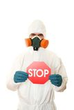 Man in protective suit with a sign STOP Royalty Free Stock Images