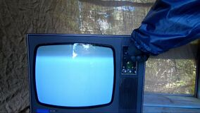 Man in protective suit switches channels on an old, retro TV