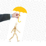 Man protects another person from adversity by covering him with an umbrella. Conceptual image with a wooden puppet Royalty Free Stock Photography