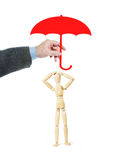 Man protects another person by covering him with an umbrella. Conceptual image with a wooden puppet Royalty Free Stock Image