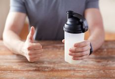 Man with protein shake bottle showing thumbs up Stock Photos