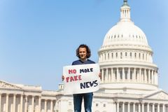Protester holding sign saying no more fake news. Man protest in front of the USA capitol in Washington holding sign saying no more fake news on social media and stock images
