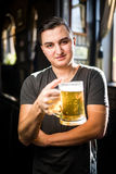 Man in a pub or bar holding mug the beer high in the air for cheers. In pub Stock Photos
