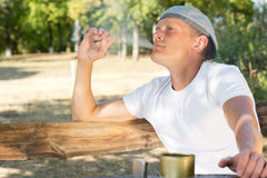 Man puffing on a cannabis or marijuana cigarette Stock Image