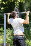 Man pull up in a park.STREET WORKOUT. Young man pull ups lever in a park Royalty Free Stock Photography