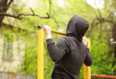 Man pulled on a horizontal bar. Exercise outdoors Stock Photos