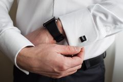 Man adjusting sleeve cuff. Man pulling on, or adjusting the cuff of his shirt sleeve stock photography