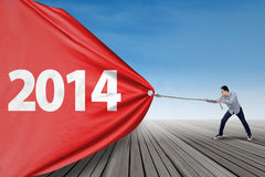 Man pulling banner of new year 2014 Stock Images
