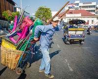 Man pulling a cart loaded with houswares crosses a busy street in Bangkok Royalty Free Stock Images