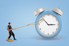 Man pulling clock hands with a rope on blue background stock photography