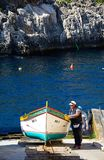 Man pulling a Dghajsa up a ramp, Blue Grotto. Men pulling a traditional Dghajsa water taxi up a ramp for mooring at the departure point, Blue Grotto, Malta Stock Photos