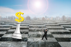 Man pulling dollar sign of money chess on chessboard Stock Photos