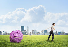 Man pulling with effort big crumpled ball of paper as creativity sign Royalty Free Stock Photos