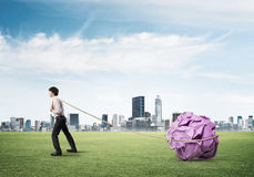 Man pulling with effort big crumpled ball of paper as creativity sign Stock Images