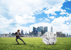 Man pulling with effort big crumpled ball of paper as creativity sign Royalty Free Stock Photography