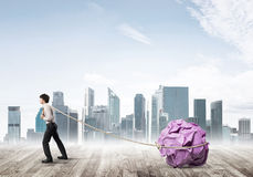 Man pulling with effort big crumpled ball of paper as creativity sign Stock Photography