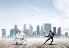Man pulling with effort big crumpled ball of paper as creativity sign Royalty Free Stock Image