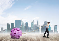 Man pulling with effort big crumpled ball of paper as creativity sign Royalty Free Stock Images