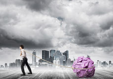 Man pulling with effort big crumpled ball of paper as creativity sign Stock Photo