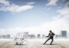 Man pulling with effort big crumpled ball of paper as creativity sign Stock Image