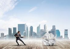 Man pulling with effort big crumpled ball of paper as creativity sign Royalty Free Stock Photo