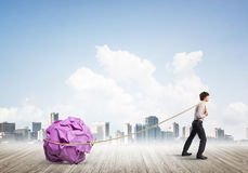 Man pulling with effort big crumpled ball of paper as creativity sign. Young businessman outdoors making huge paper ball move Stock Images