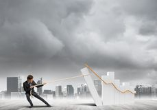 Man pulling with effort big pulling rope graph, as a symbol of financial growth. Young businessman outdoors making huge graph move Royalty Free Stock Images