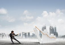 Man pulling with effort big pulling rope graph, as a symbol of financial growth. Young businessman outdoors making huge graph move Stock Photo