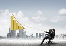 Man pulling with effort big pulling rope graph, as a symbol of financial growth Stock Image